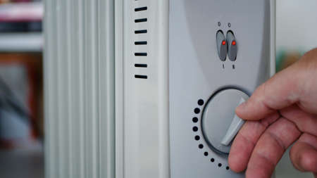 Man Sets the Heating Temperature of an Electric Radiator at Home in a Cold Room