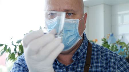 Image with a Bartender Wearing Protective Gloves and Face Mask Cleaning a Glass Imagens