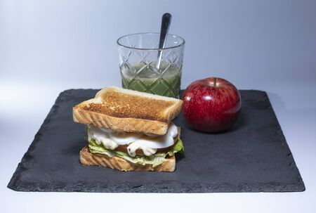 Vegetable sandwich with egg, lettuce and tomato and juice. Accompanied by an apple. Healthy food for confinement
