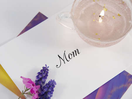 A Mothers Day card and envelope with flowers and candle. Stock Photo