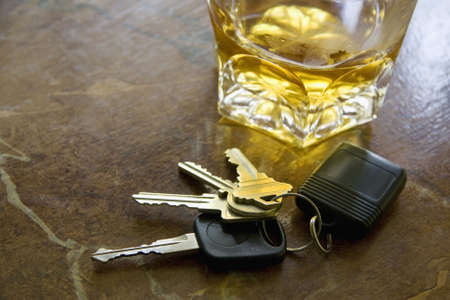 Close-up of car keys with unfinished drink on table.