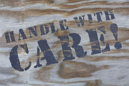 handle with care: Close-up of handle with care sign on shipping carton. Stock Photo