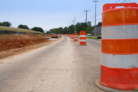 A row of traffic cones indicate road construction.