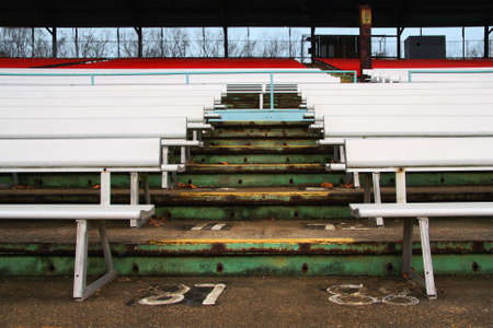 Old weathered steps and seats in an empty stadium.