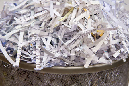 Closeup of shredded paper in a wastebasket.