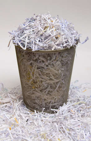A waste basket overflowing with shredded paper.
