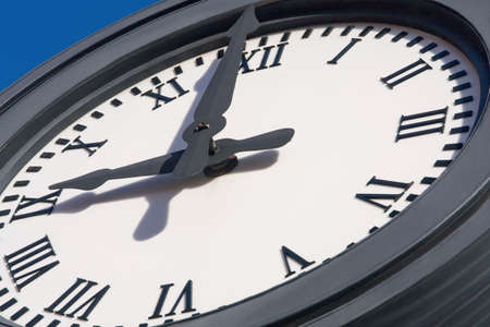 Large clock face with roman numerals outdoors. photo