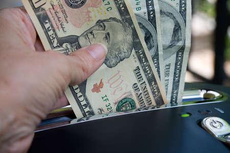 Female hand putting money through a shredder. photo