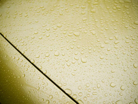 Gold waxed car hood with water drops. Stok Fotoğraf