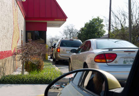vehicle window: Knoxville, Tennessee, USA - March 13, 2011: A line of cars waits at a busy Hardees Restaurant Drive-Thru at lunch time.