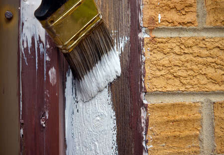 renovations: Paintbrush applying primer to wood trim. Stock Photo