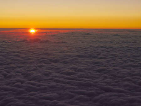 Orange sunrise seen from above the clouds photo