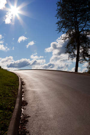 convergence: Perspective of paved road with sun and sky Stock Photo