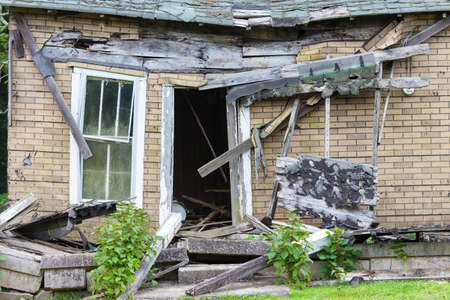 deteriorating: Front of an abandoned house that is falling down