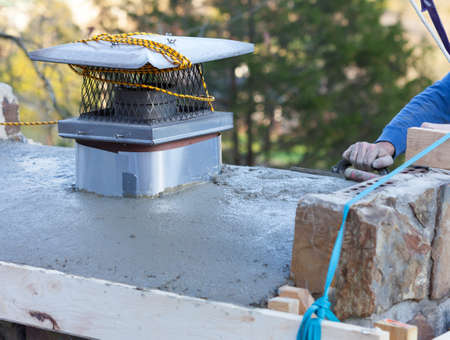 workingman: Man using cement to repair the crown of a house chimney