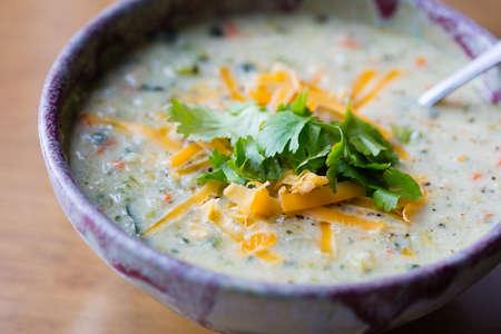 perejil: Tazón de sopa de coliflor con queso cheddar rallado y guarnición de cilantro