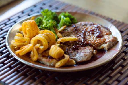 pork chops: Grilled pork chops with curly fries and steamed broccoli