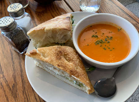 A beautiful meal with a gourmet grilled cheese sandwich made with homemade herbed focaccia bread, cheddar, goat cheese, sprouts, apples, along with creamy tomato soup. Stok Fotoğraf