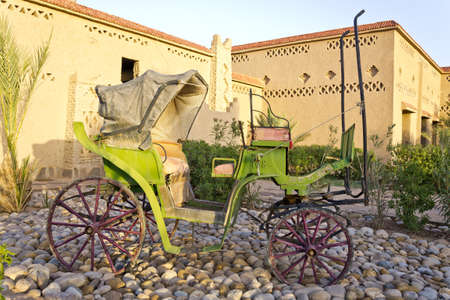 Old carriage standing on a garden at the desert photo