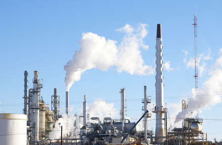 Oil refinery smoke stacks and machinery against blue sky.