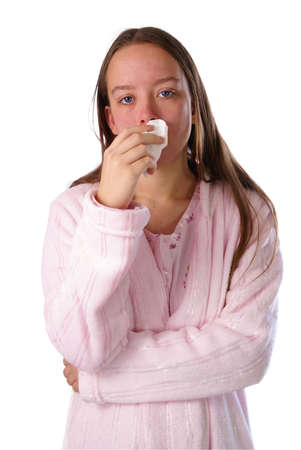 Cold and Flu season. Teen girl in nightgown and robe holds tissue to her nose.