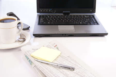 Office desk with laptop computer, newspapers, coffee and misc work materials