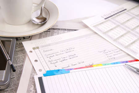 Office desk with womans daily schedule and misc work materials