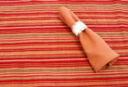 napkin ring: Cloth napkin with decorative napkin ring on striped placemat