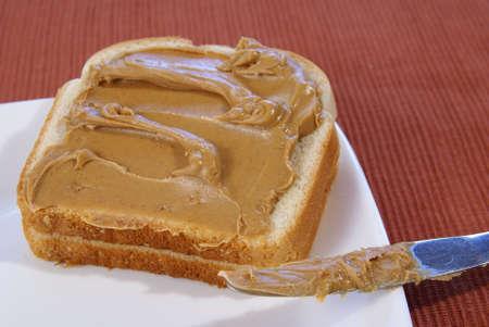 Creamy peanut butter on bread. Stock Photo