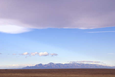 nm: New Mexico scenic travel. Pink tinged Mountain and clouds in south east NM USA. Route 285 between Roswell and Vaughn