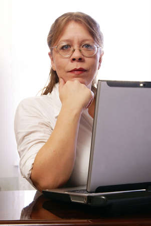 Woman wearing eyeglasses and white blouse working on laptop computer at home. Stock Photo - 2458028