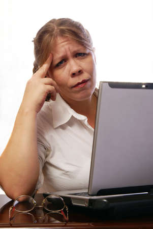 Woman with headache or stress wearing white blouse working on laptop computer Stock Photo - 2458030
