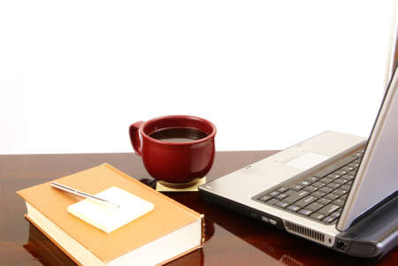 Laptop computer, coffee, book with sticky notes and pen on top of dark wood desk. Stock Photo