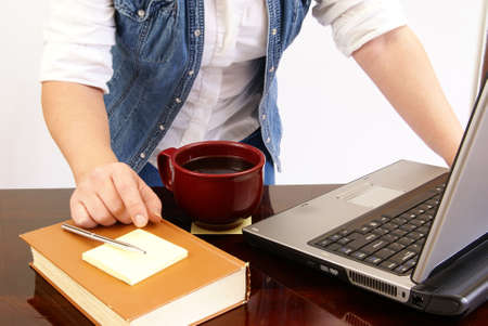 Womans torso leaning over a laptop on desk with book, pen, paper, and coffee. photo
