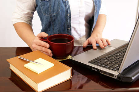 Woman working at a laptop on desk with book, pen, paper, and coffee. photo