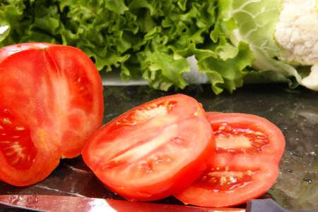 Fresh sliced ripe tomatoes on black marble cutting board.