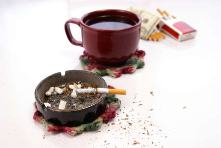 Filthy habit and lifestyle concept with cigarette, dirty ashtray and table, coffee, and related items. photo
