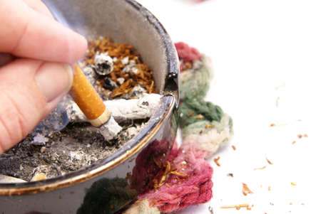 burning money: Filthy habit and lifestyle concept with cigarette, dirty ashtray and table, coffee, and related items.
