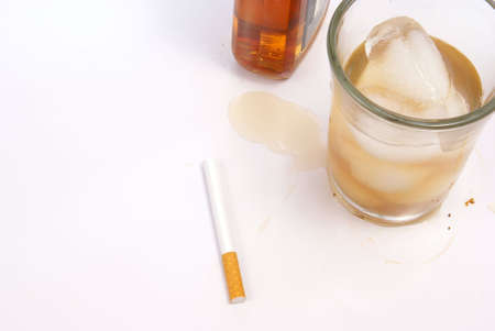 Bad habits concept with glass of whiskey next to a cigarette on dirty white table.