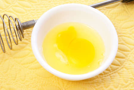 Raw egg in bowl on yellow placemat