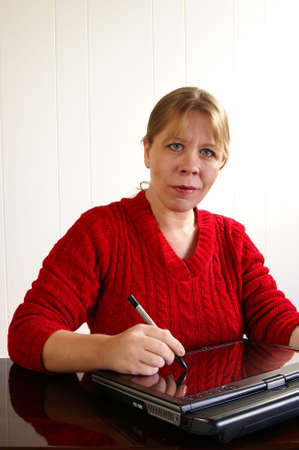 Woman in red sweater writing with stylus on a tablet pc Stock Photo - 2513669