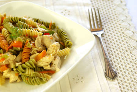 Colorful fresh pasta salad with chicken breast and fresh garden vegetables, tossed in moist salad dressing.