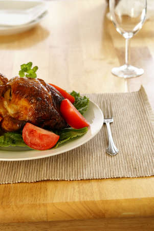 Whole roasted chicken on bed of lettuce with tomatoe wedges.