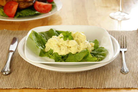 Mustard style potato salad on bed of lettuce greens. Stock Photo