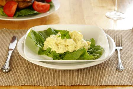 Mustard style potato salad on bed of lettuce greens. Stock Photo
