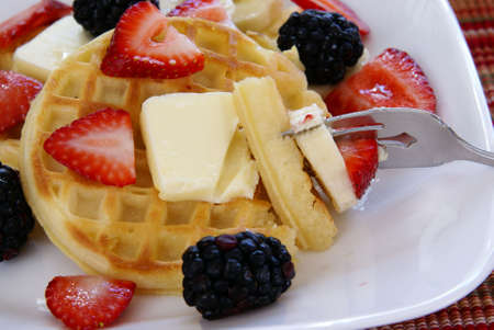 Close up of Waffles with strawberries, blackberries, bananas, butter, and light vanilla syrup.