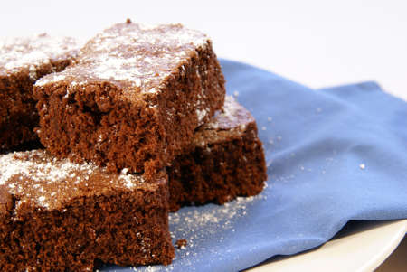 powdered sugar: Thick chocolate fudge brownies with powdered sugar sprinkled on top. Stock Photo