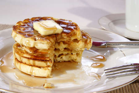 Stack of fresh cooked breakfast waffles with butter and syrup, partially eaten