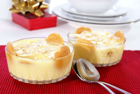 Old fashioned banana pudding with cookies, banana chunks, and pudding in cut crystal dishes on Christmas decorated table Stock Photo - 2526084