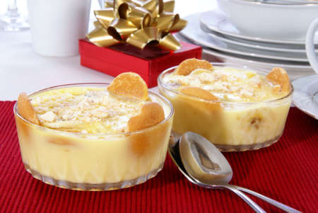Old fashioned banana pudding with cookies, banana chunks, and pudding in cut crystal dishes on Christmas decorated table